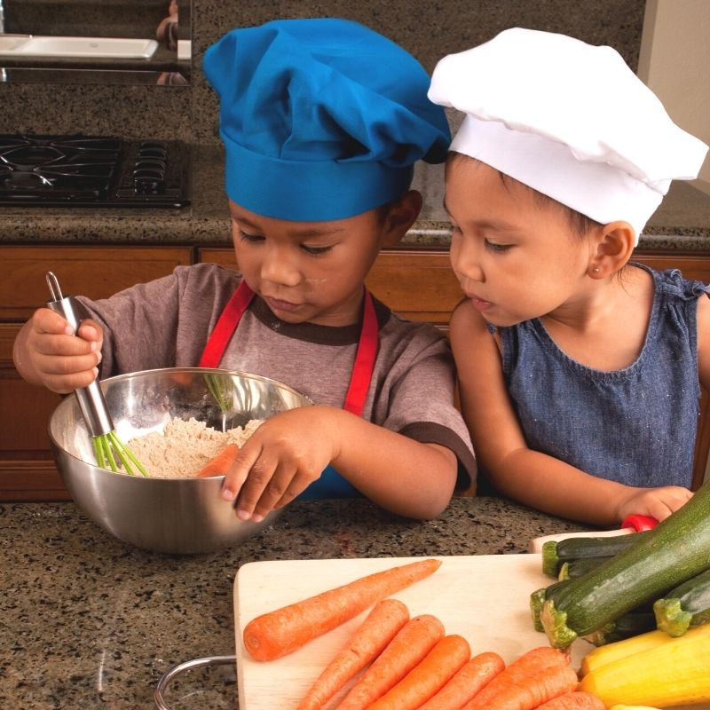 Children in chef hats cooking together.